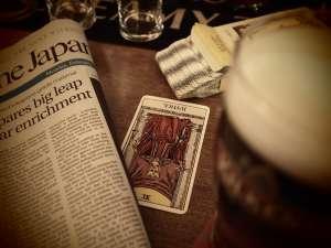 une carte de tarot utilisée en voyance à coté d'un journal sur une table